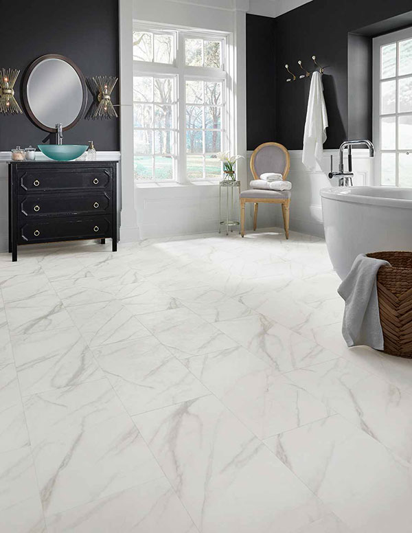 Modern 2020 bathroom designed with a high-contrast theme utilizing dark painted walls and cabinets, on white tile floors.