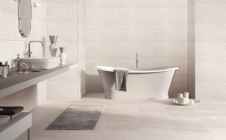 Modern home bathroom with large white soaking tub, a white washbowl sink on a grey countertop, and tiled floor and walls.